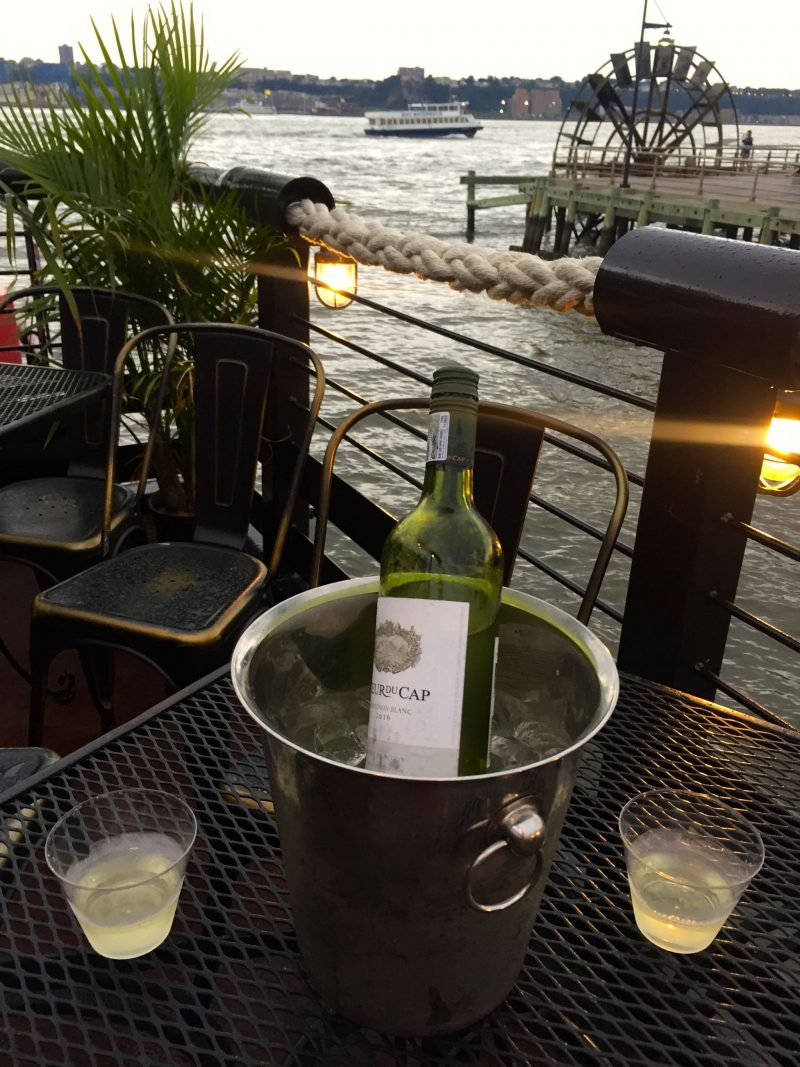 Drinking a bottle of wine at the Frying Pan in New York City in the summer.
